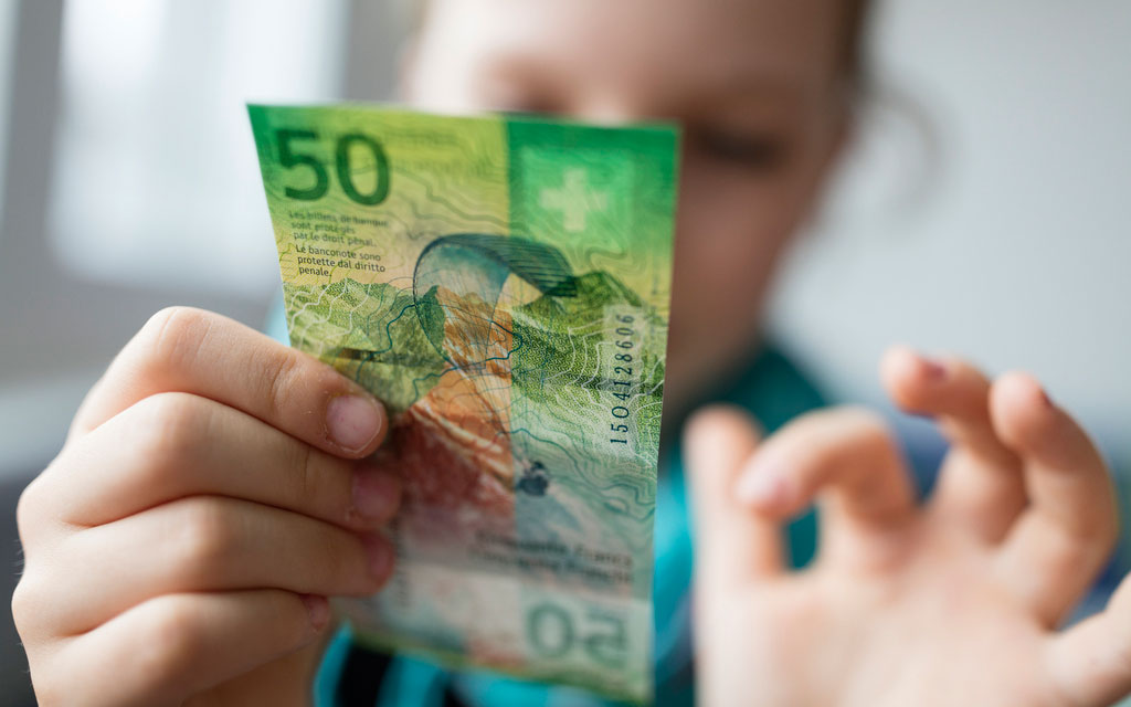 A child examines a 50-franc banknote