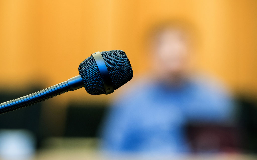 A blurred image of a witness behind a microphone in a courtroom